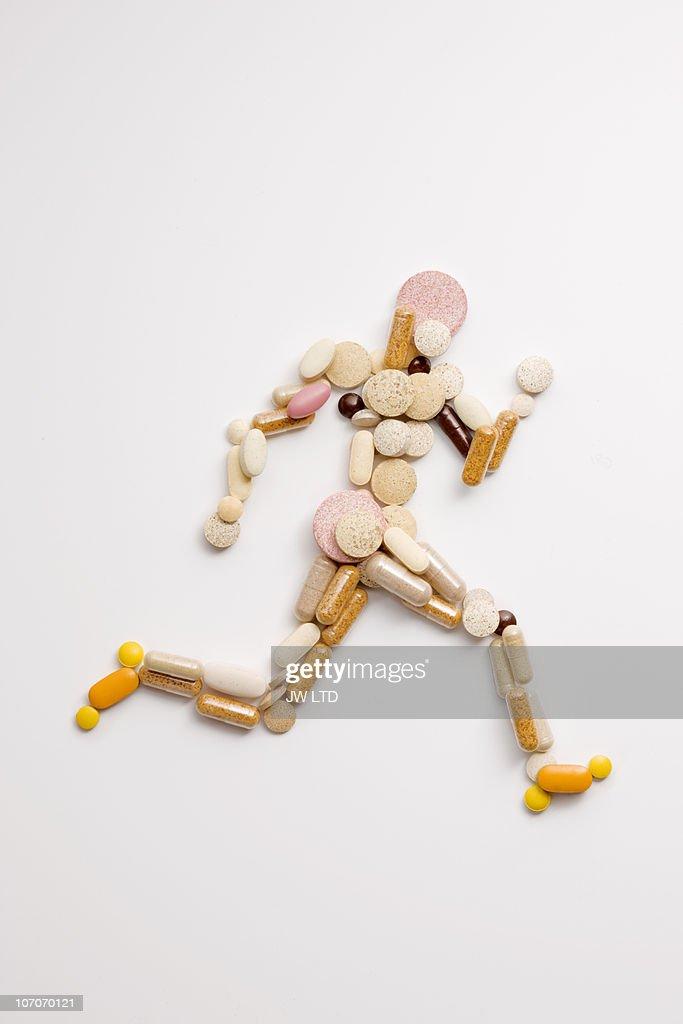 Vitamin pills in shape of man running