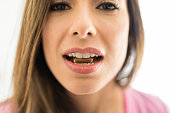 Closeup of woman with cod liver oil capsule in mouth at home