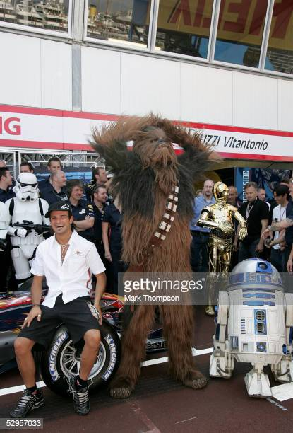 Vitantonio Liuzzi of Italy and Red Bull poses with Star Wars characters Chewbacca and R2D2 outside the Red Bull Racing team garage during the...