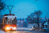 Vitebsk, Belarus. Public Old Retro Tram Of Route Number Eight Moving Near Private Sector And Old Cathedral Of St. Barbara In Evening Night Illuminations At Winter.