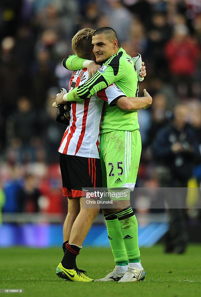 Vito Mannone (R) of Sunderland embraces Sebastian Larsson at full-time following the Barclays Premier League match between Sunderland and Manchester City at Stadium of Light on November 10, 2013 in Sunderland, England.