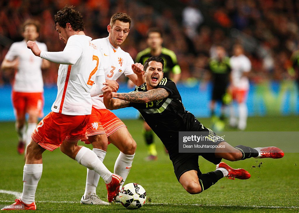Vitolo of Spain goes to ground challenged by <a gi-track='captionPersonalityLinkClicked' href=/galleries/search?phrase=Daryl+Janmaat&family=editorial&specificpeople=6134960 ng-click='$event.stopPropagation()'>Daryl Janmaat</a> (L) and Stefan de Vrij of Netherlands during the international friendly match between the Netherlands and Spain held at Amsterdam Arena on March 31, 2015 in Amsterdam, Netherlands.