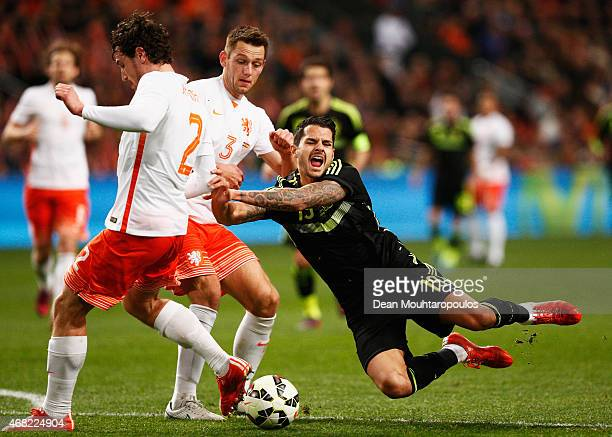 Vitolo of Spain goes to ground challenged by Daryl Janmaat and Stefan de Vrij of Netherlands during the international friendly match between the...