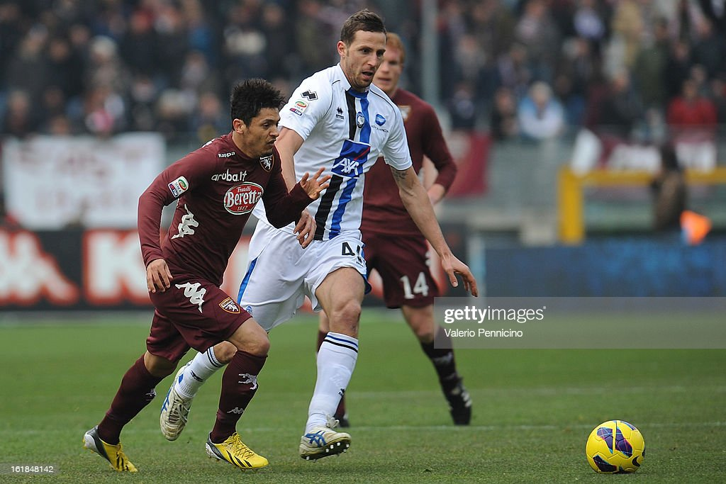 Vitor Barreto (L) of Torino FC is challenged by Riccardo Cazzola of Atalanta BC during the Serie A match between Torino FC and Atalanta BC at Stadio Olimpico di Torino on February 17, 2013 in Turin, Italy.