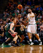 Vitor Faverani of the Boston Celtics passes the ball in front of John Henson of the Milwaukee Bucks in the second half during the home opener at TD...