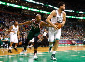 Vitor Faverani of the Boston Celtics rebounds a ball in front of Caron Butler of the Milwaukee Bucks in the second half during the home opener at TD...