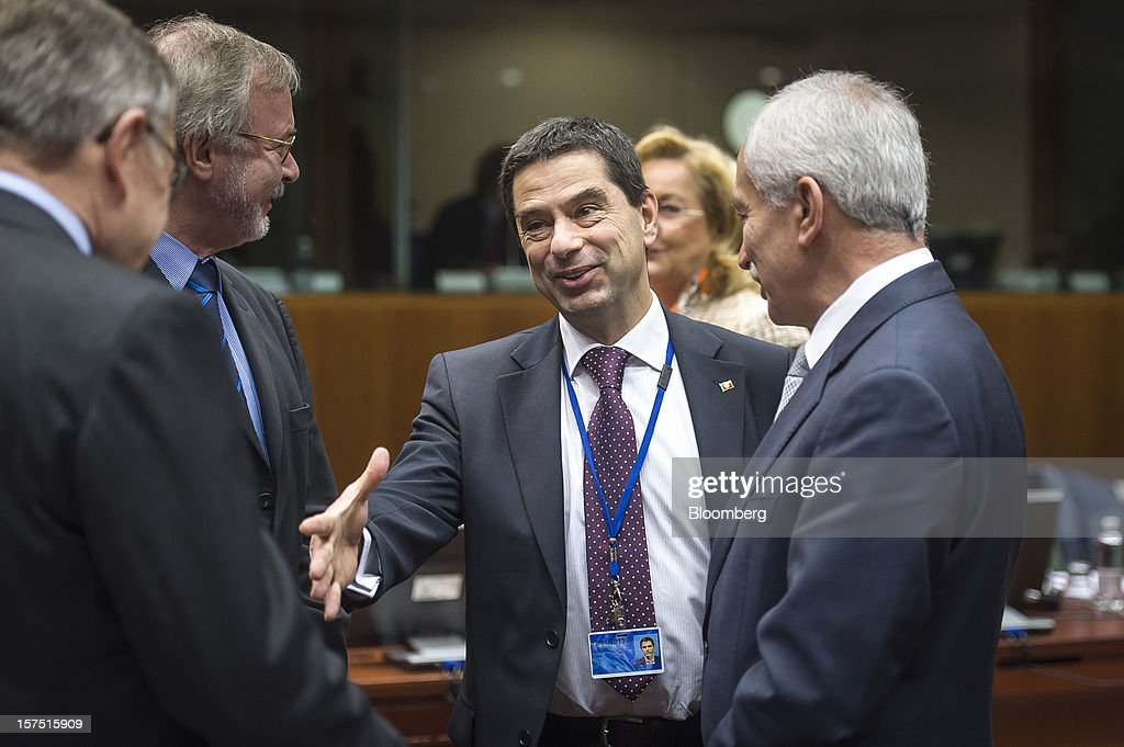 Vitor Gaspar, Portugal's finance minister, center, greets Klaus Regling, chief executive officer of the European Stability Mechanism, left, Werner Hoyer, president of the European Investment Bank, second left, and Vassos Shiarly, Cyprus' finance minister, during a meeting of European Union (EU) finance ministers at the European Council headquarters in Brussels, Belgium, on Tuesday, Dec. 4, 2012. European finance ministers voiced confidence that Greece will pull off a successful bond buyback, the key element in a revamped effort to stem the debt crisis in the country where it started. Photographer: Jock Fistick/Bloomberg via Getty Images