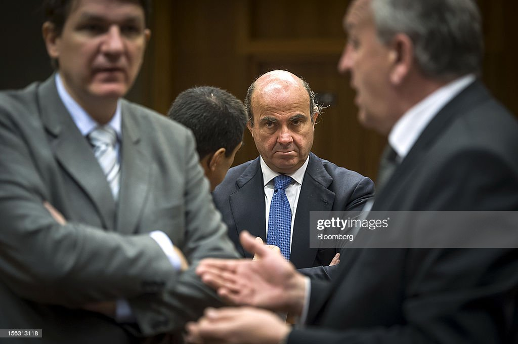 Vitor Gaspar, Portugal's finance minister, center left, speaks with <a gi-track='captionPersonalityLinkClicked' href=/galleries/search?phrase=Luis+de+Guindos&family=editorial&specificpeople=8756055 ng-click='$event.stopPropagation()'>Luis de Guindos</a>, Spain's economy minister, center right, ahead of a European Union (EU) finance ministers meeting at the European Council headquarters in Brussels, Belgium, on Tuesday, Nov. 13, 2012. Euro-area finance ministers gave Greece two extra years to wrestle down its budget deficit, pledging to plug the resulting financing gaps in order to keep the country in the single currency and prevent a renewed flareup of the debt crisis. Photographer: Jock Fistick/Bloomberg via Getty Images