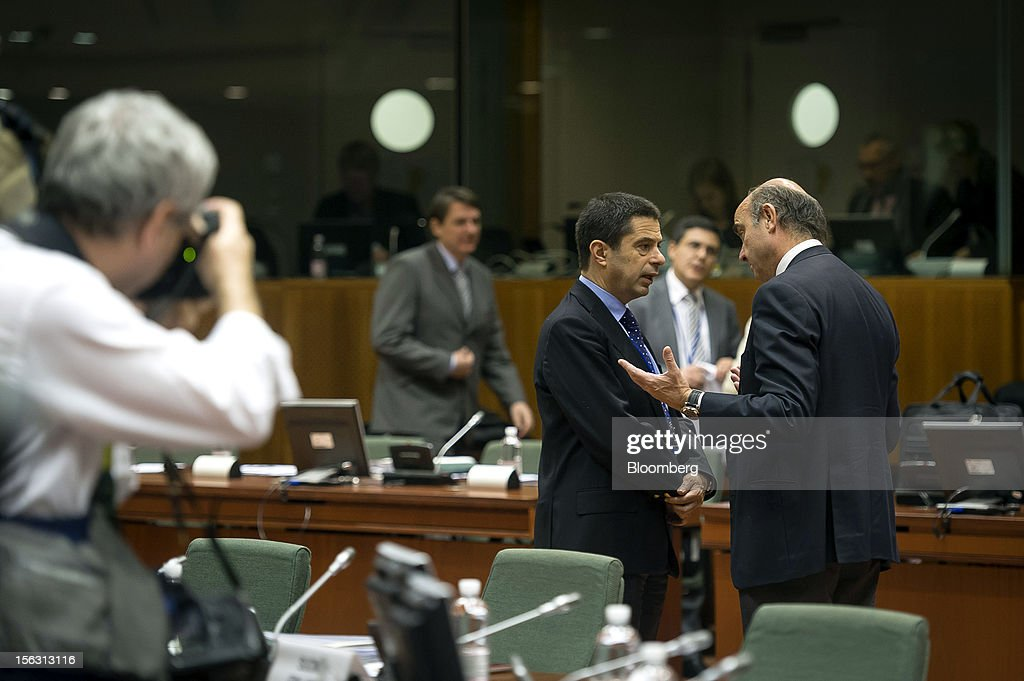 Vitor Gaspar, Portugal's finance minister, center, speaks with <a gi-track='captionPersonalityLinkClicked' href=/galleries/search?phrase=Luis+de+Guindos&family=editorial&specificpeople=8756055 ng-click='$event.stopPropagation()'>Luis de Guindos</a>, Spain's economy minister, right, ahead of a European Union (EU) finance ministers meeting at the European Council headquarters in Brussels, Belgium, on Tuesday, Nov. 13, 2012. Euro-area finance ministers gave Greece two extra years to wrestle down its budget deficit, pledging to plug the resulting financing gaps in order to keep the country in the single currency and prevent a renewed flareup of the debt crisis. Photographer: Jock Fistick/Bloomberg via Getty Images
