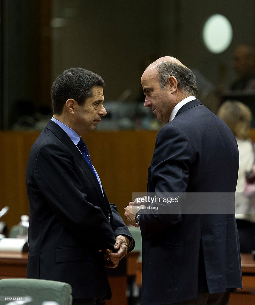 Vitor Gaspar, Portugal's finance minister, left, speaks with <a gi-track='captionPersonalityLinkClicked' href=/galleries/search?phrase=Luis+de+Guindos&family=editorial&specificpeople=8756055 ng-click='$event.stopPropagation()'>Luis de Guindos</a>, Spain's economy minister, ahead of a European Union (EU) finance ministers meeting at the European Council headquarters in Brussels, Belgium, on Tuesday, Nov. 13, 2012. Euro-area finance ministers gave Greece two extra years to wrestle down its budget deficit, pledging to plug the resulting financing gaps in order to keep the country in the single currency and prevent a renewed flareup of the debt crisis. Photographer: Jock Fistick/Bloomberg via Getty Images