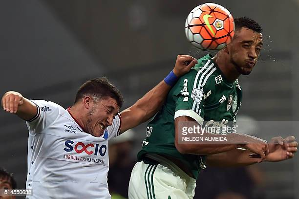 Vitor Hugo of Brazils Palmeiras heads for the ball with Luis Espino of Uruguay's Nacional during their 2016 Copa Libertadores football match held at...