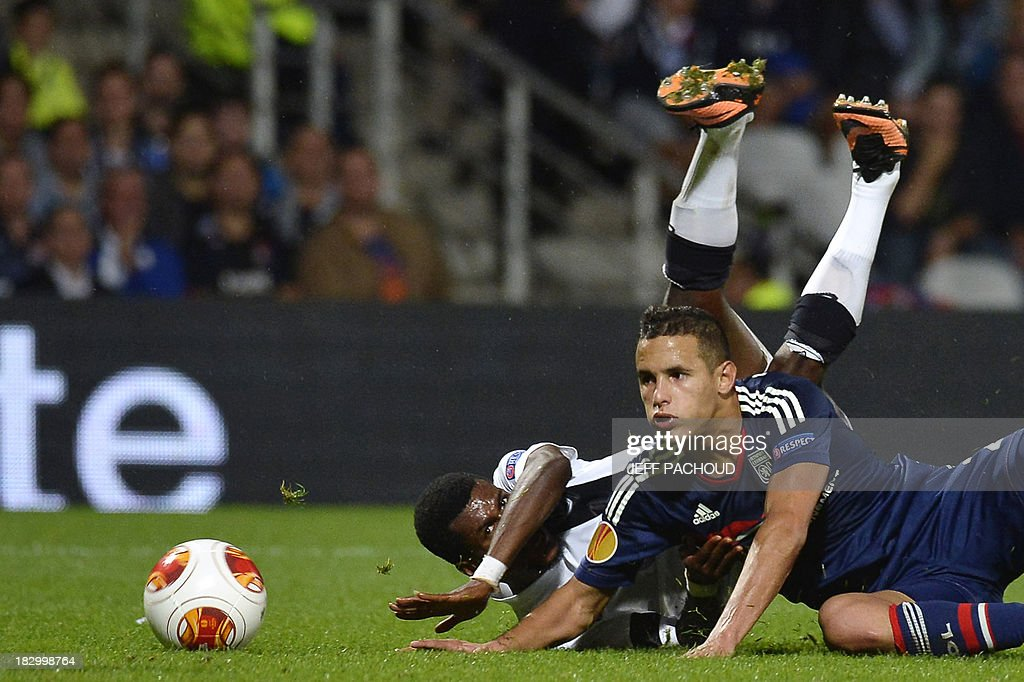Vitoria Guimaraes' Burkinabe forward Nii Plange (L) falls with Lyon's French defender Mehdi Zeffane (R) during the UEFA Europa League group I football match Olympique Lyonnais (OL) vs Vitoria Guimaraes on October 3, 2013, at the Gerland Stadium in Lyon, central-eastern France.