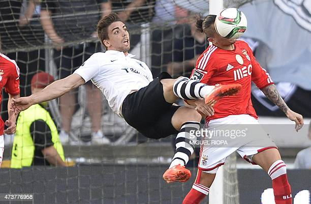 Vitoria SC's forward Tomane tries to kick the ball next to Benfica's Serbian midfielder Ljubomir Fejsa during the Portuguese league football match...