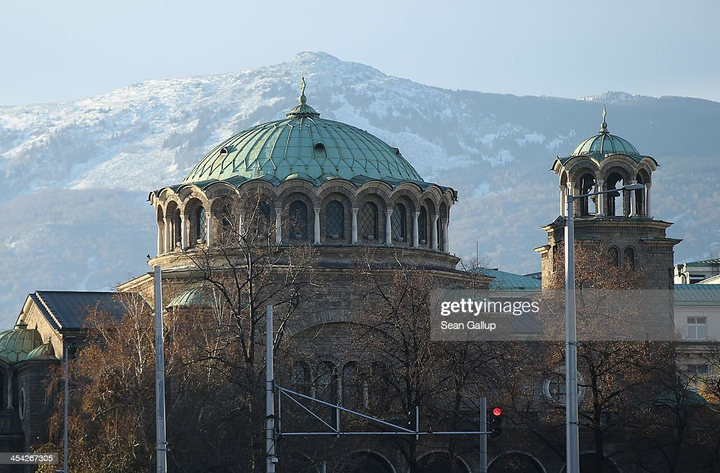 Vitosha Mountain looms behind St Nedelya Eastern Orthodox church on December 8, 2013 in Sofia, Bulgaria. Sofia is becoming an increasingly popular tourit destination.