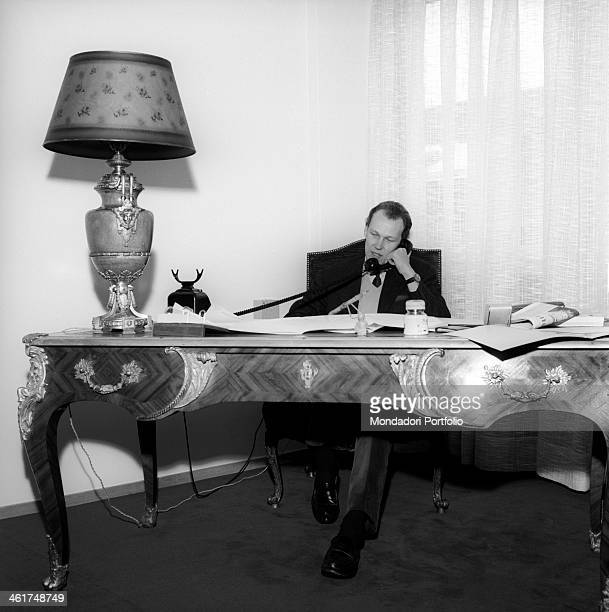 Vittorio Emanuele of Savoy son of the last king of Italy sits at a Louis XV desk and talks on the phone with a prospective buyer uninterested in the...