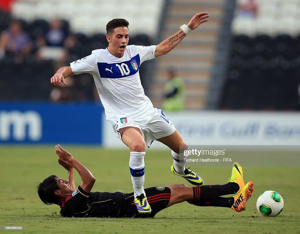 Vittorio Parigini of Italy is tackled by Erick Aguirre of Mexico during the FIFA U-17 World Cup UAE 2013 Round of 16 match between Italy and Mexico at the Mohamed Bin Zayed Stadium on October 28, 2013 in Abu Dhabi, United Arab Emirates.