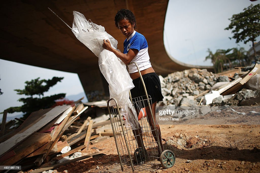 Viviane Sabino de Souza collects recyclable metal near her makeshift dwelling on a stretch of the Transcarioca BRT (Bus Rapid Transit) highway being constructed on May 22, 2014 in Rio de Janeiro, Brazil. De Souza says her parents were killed in flooding north of Rio de Janeiro, leaving her homeless last year. She has lived beneath the stretch of new highway for about six weeks and is awaiting government assistance for new identification papers. De Souza earns money partially by collecting recyclable materials discarded from construction of the highway. The Transcarioca is part of the larger BRT system being constructed which will link Rio's international airport with Barra da Tijuca, the main site of the Rio 2016 Olympic Games. The city is taking on a number of infrastructure projects ahead of the 2014 FIFA World Cup and Rio 2016 Olympic Games.