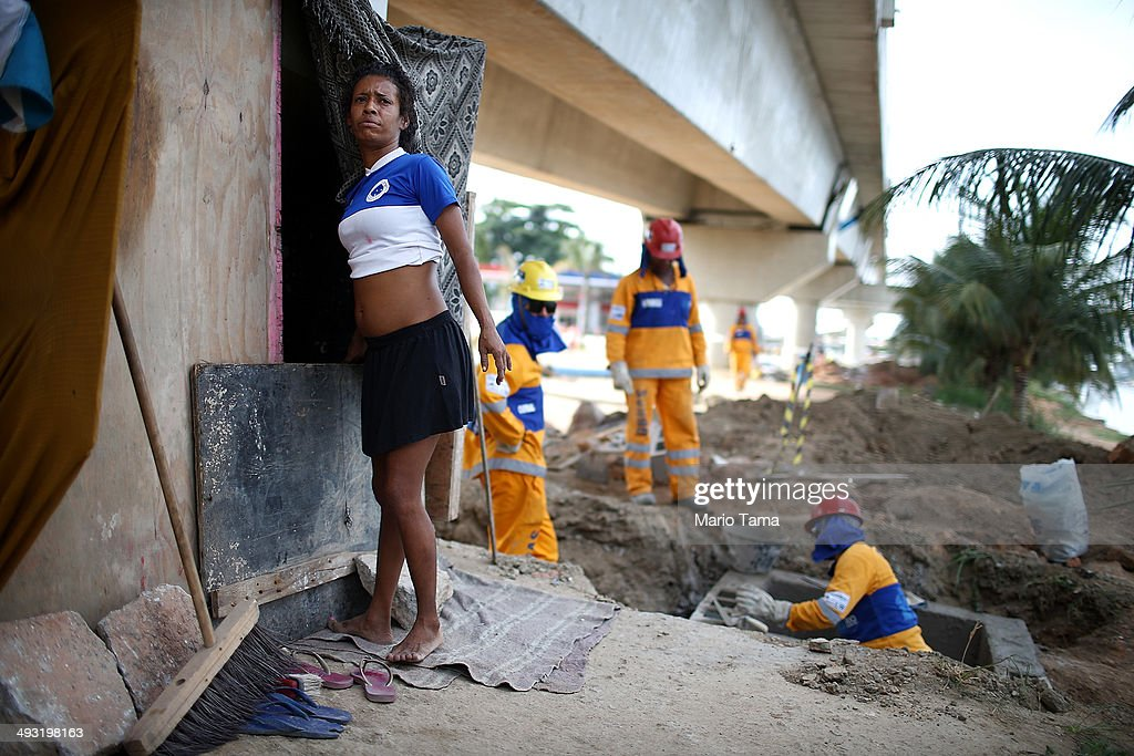 Viviane Sabino de Souza pauses outside her makeshift dwelling next to construction workers on a stretch of the Transcarioca BRT (Bus Rapid Transit) highway being constructed on May 22, 2014 in Rio de Janeiro, Brazil. De Souza says her parents were killed in flooding north of Rio de Janeiro, leaving her homeless last year. She has lived beneath the stretch of new highway for about six weeks and awaits government assistance in procuring new identification papers. De Souza earns money partially by collecting recyclable materials discarded from construction of the highway. The Transcarioca is part of the larger BRT system being constructed which will link Rio's international airport with Barra da Tijuca, the main site of the Rio 2016 Olympic Games. The city is taking on a number of infrastructure projects ahead of the 2014 FIFA World Cup and Rio 2016 Olympic Games.