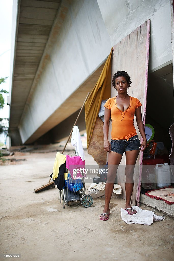 Viviane Sabino de Souza poses in front of her makeshift dwelling beneath a stretch of the Transcarioca BRT (Bus Rapid Transit) highway being constructed on May 9, 2014 in Rio de Janeiro, Brazil. De Souza says her parents were killed in flooding north of Rio de Janeiro, leaving her homeless last year. She has lived beneath the stretch of new highway for about a month and needs government assistance in procuring new identification papers. The Transcarioca is part of the larger BRT system being constructed which will link Rio's international airport with Barra da Tijuca, the main site of the Rio 2016 Olympic Games. The city is moving ahead on a number of infrastructure projects ahead of the 2014 FIFA World Cup and Rio 2016 Olympic Games.