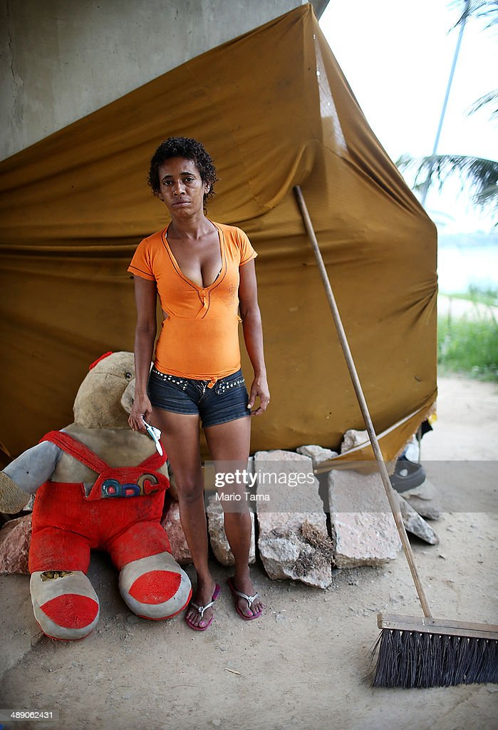 Viviane Sabino de Souza poses outside her makeshift dwelling beneath a stretch of the Transcarioca BRT (Bus Rapid Transit) highway being constructed on May 9, 2014 in Rio de Janeiro, Brazil. De Souza says her parents were killed in flooding north of Rio de Janeiro, leaving her homeless last year. She has lived beneath the stretch of new highway for about a month and needs government assistance in procuring new identification papers. The Transcarioca is part of the larger BRT system being constructed which will link Rio's international airport with Barra da Tijuca, the main site of the Rio 2016 Olympic Games. The city is moving ahead on a number of infrastructure projects ahead of the 2014 FIFA World Cup and Rio 2016 Olympic Games.