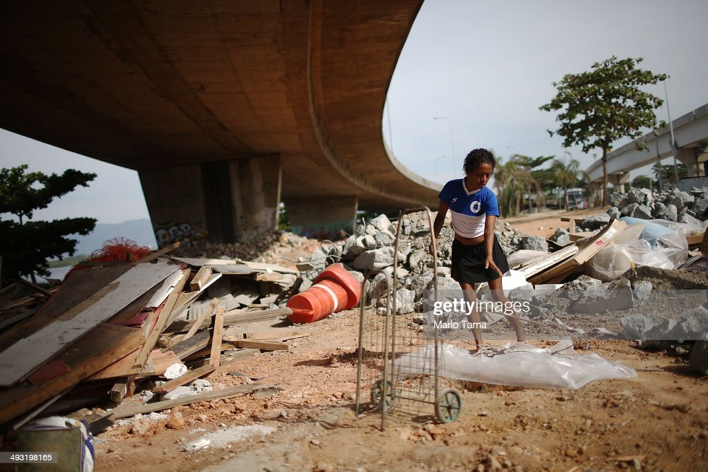 Viviane Sabino de Souza searches for recyclable metal near her makeshift dwelling beneath a stretch of the Transcarioca BRT (Bus Rapid Transit) highway being constructed on May 22, 2014 in Rio de Janeiro, Brazil. De Souza says her parents were killed in flooding north of Rio de Janeiro, leaving her homeless last year. She has lived beneath the stretch of new highway for about six weeks and is awaiting government assistance for new identification papers. De Souza earns money partially by collecting recyclable materials discarded from construction of the highway. The Transcarioca is part of the larger BRT system being constructed which will link Rio's international airport with Barra da Tijuca, the main site of the Rio 2016 Olympic Games. The city is taking on a number of infrastructure projects ahead of the 2014 FIFA World Cup and Rio 2016 Olympic Games.