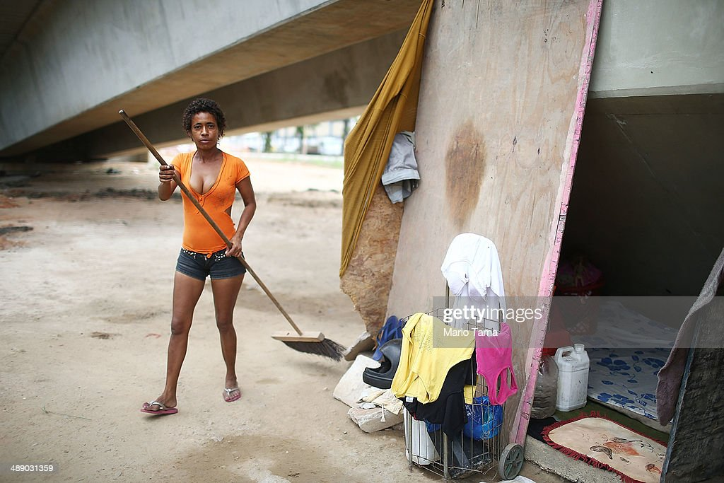 Viviane Sabino de Souza sweeps outside her makeshift dwelling beneath a stretch of the Transcarioca BRT (Bus Rapid Transit) highway being constructed on May 9, 2014 in Rio de Janeiro, Brazil. De Souza says her parents were killed in flooding north of Rio de Janeiro, leaving her homeless last year. She has lived beneath the stretch of new highway for about a month and needs government assistance in procuring new identification papers. The Transcarioca is part of the larger BRT system being constructed which will link Rio's international airport with Barra da Tijuca, the main site of the Rio 2016 Olympic Games. The city is taking on a number of infrastructure projects ahead of the 2014 FIFA World Cup and Rio 2016 Olympic Games.