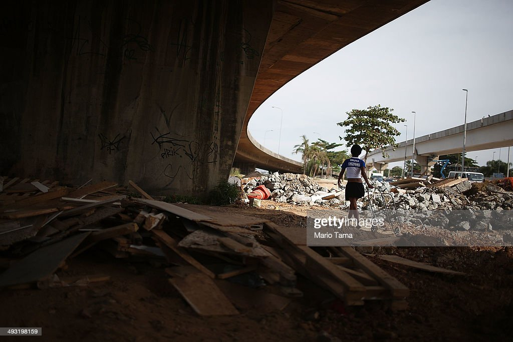 Viviane Sabino de Souza walks with her cart while searching for recyclable metal near her makeshift dwelling on a stretch of the Transcarioca BRT (Bus Rapid Transit) highway being constructed on May 22, 2014 in Rio de Janeiro, Brazil. De Souza says her parents were killed in flooding north of Rio de Janeiro, leaving her homeless last year. She has lived beneath the stretch of new highway for about six weeks and is awaiting government assistance for new identification papers. De Souza earns money partially by collecting recyclable materials discarded from construction of the highway. The Transcarioca is part of the larger BRT system being constructed which will link Rio's international airport with Barra da Tijuca, the main site of the Rio 2016 Olympic Games. The city is taking on a number of infrastructure projects ahead of the 2014 FIFA World Cup and Rio 2016 Olympic Games.