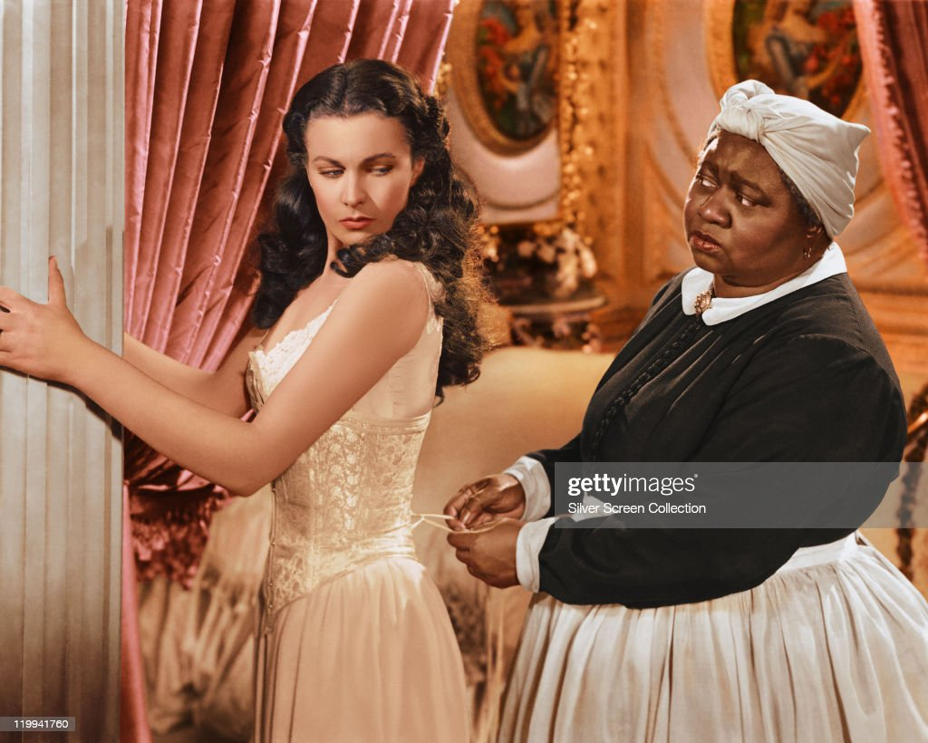 Vivien Leigh British actress has her corset tightened by Hattie McDaniel US actress in a publicity still issued for the film 'Gone with the Wind'...