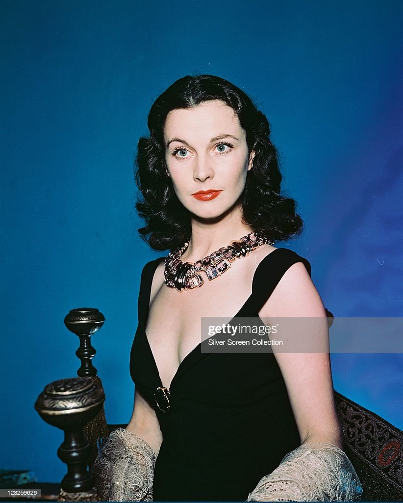 Vivien Leigh (1913-1967), British actress, wearing a black dress with a plunging neckline, and an ornate necklace, in a studio portrait, against a blue background, circa 1940.
