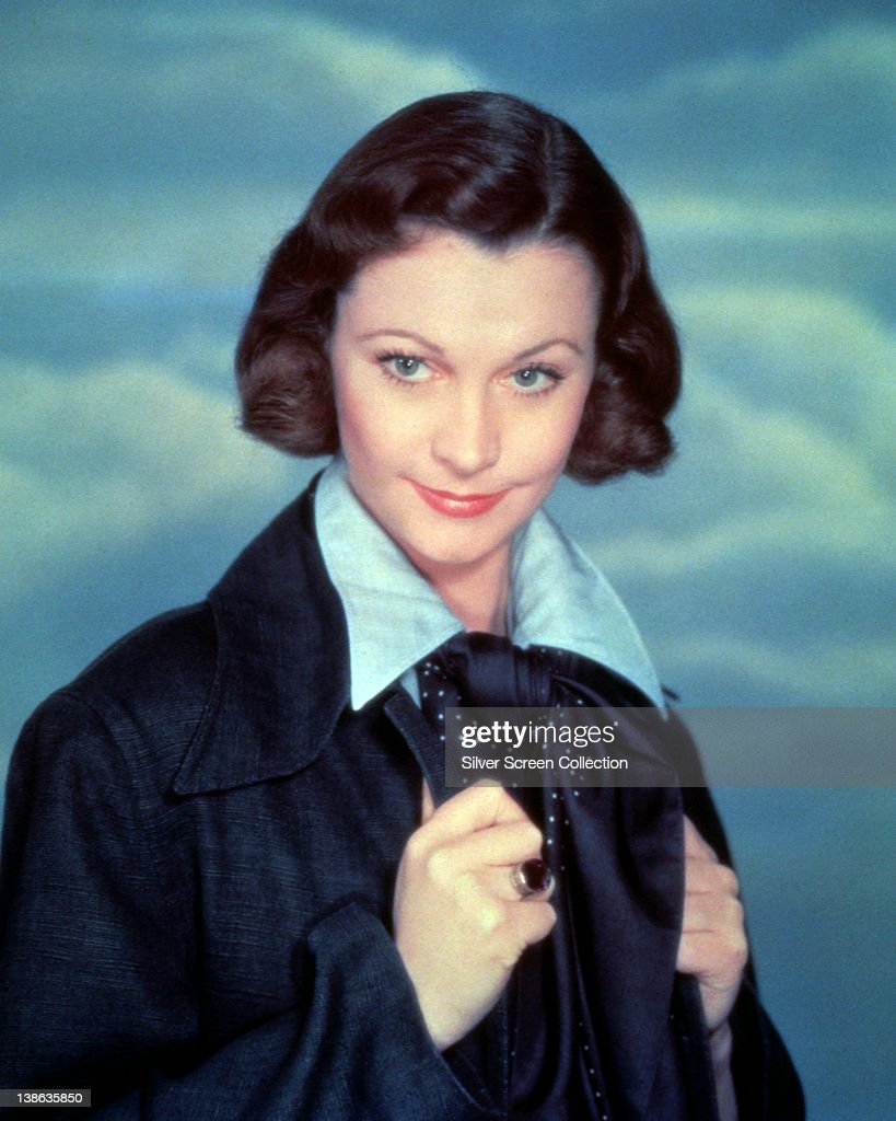 Vivien Leigh (1913-1967), British actress, wearing a dark blue jacket over a light blue shirt in a studio portrait, against a background of blue sky and clouds, circa 1940.