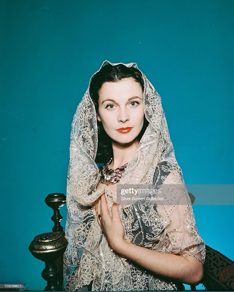 Vivien Leigh (1913-1967), British actress, wearing a white lace veil in a studio portrait, against a blue background, circa 1940.