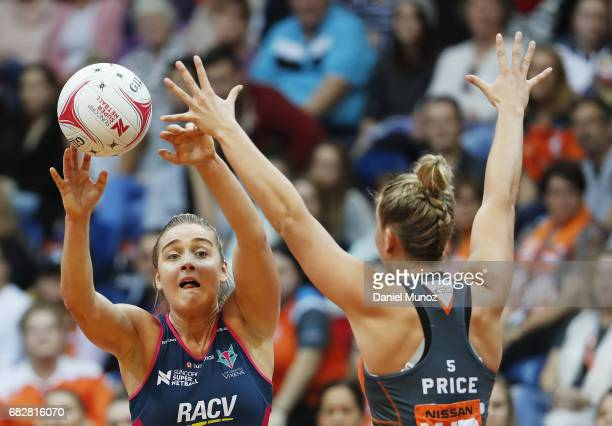 Vixens wing attack Liz Watson passes the ball evading wing defence JamieLee Price during the round 12 Super Netball match between the Giants and the...