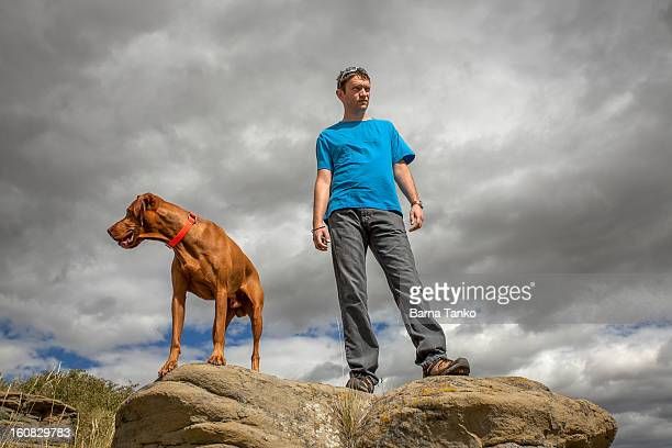Vizsla dog and young man standing on top of cliff