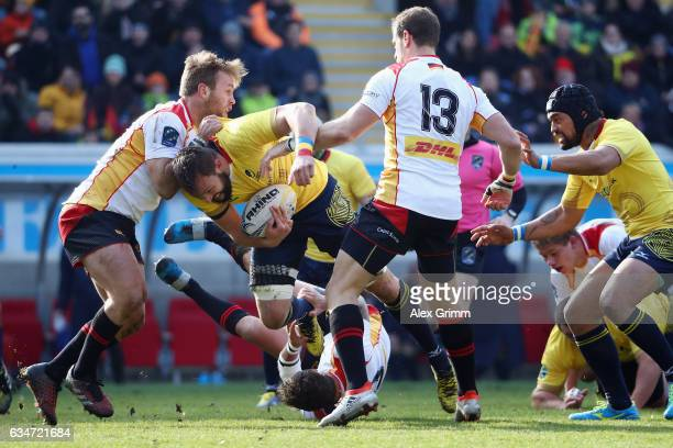 Vlad Nistor of Romania is challenged by Jacobus Otto and Clemens von Grumbkow of Germany during the European Shield Rugby match between Germany and...