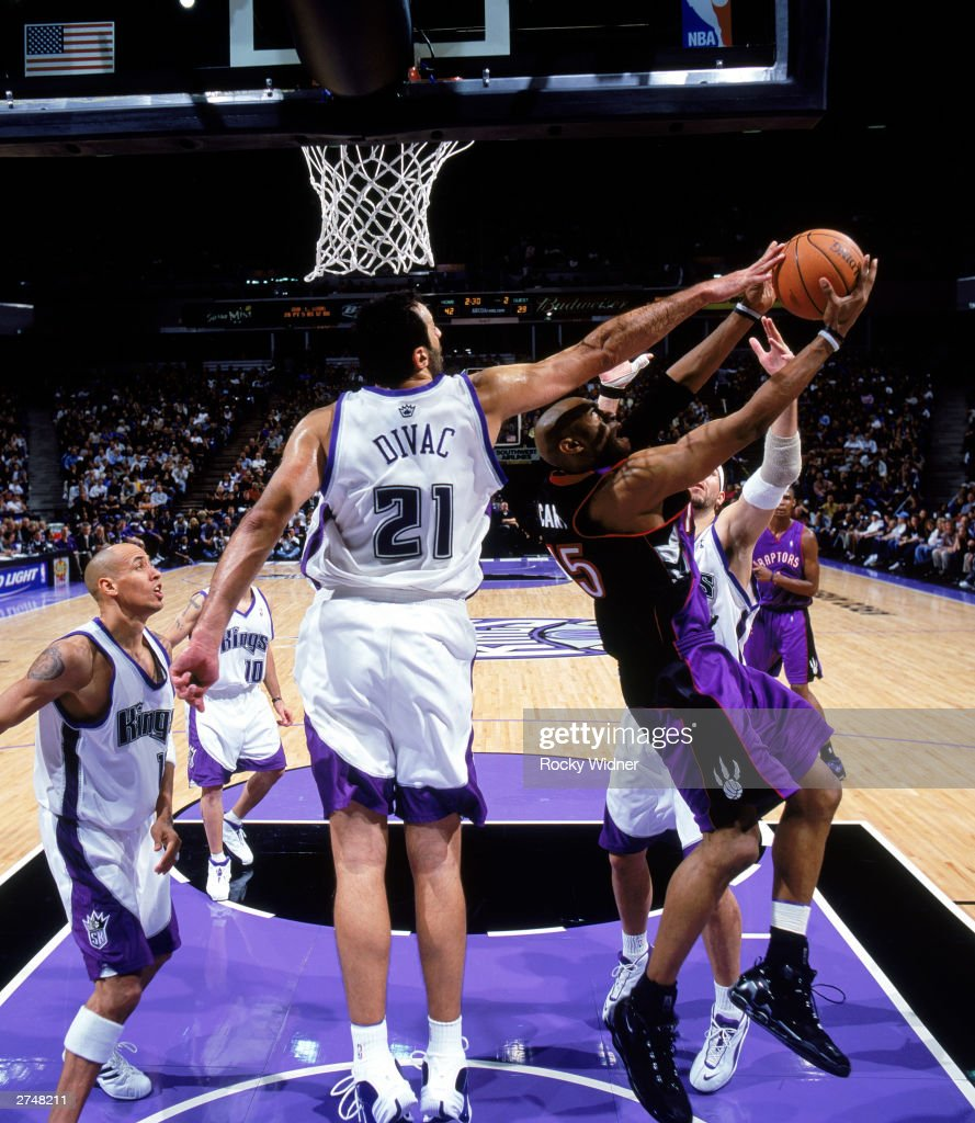 Vlade Divac #21 of the Sacramento Kings blocks a shot by Vince Carter #15 of the Toronto Raptors during the NBA game at Arco Arena on November 14, 2003 in Sacramento, California. The Kings won 94-64.