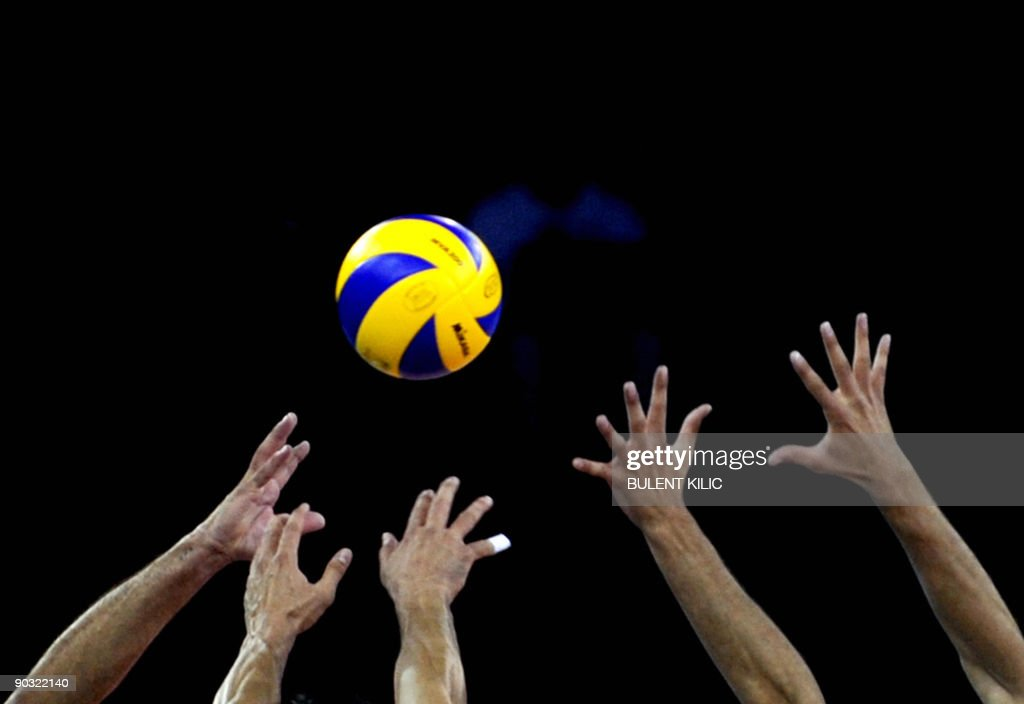Vlademir Nikolov of Bulgaria spikes the ball over the net blocked by Serbia's Bojan Janic and Marko Podrascanin during their European Volleyball...