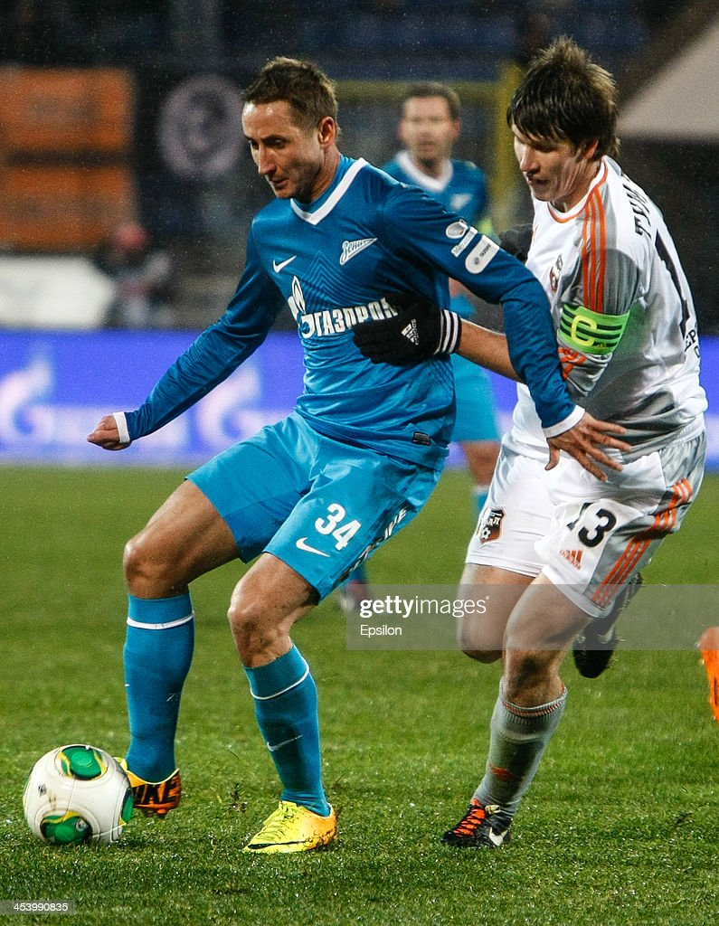 Vladimir Bystrov of FC Zenit St. Petersburg (L) and Denis Tumasyan of FC Ural Sverdlovsk Oblast vie for the ball during the Russian Football League Championship match between FC Zenit St. Petersburg and FC Ural Sverdlovsk Oblast at the Petrovsky stadium on December 6, 2013 in St. Petersburg, Russia.