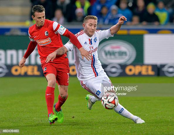Vladimir Dariada of Freiburg challenges Lewis Holtby of Hamuburger SV during the Bundesliga match between SC Freiburg and Hamburger SV at...