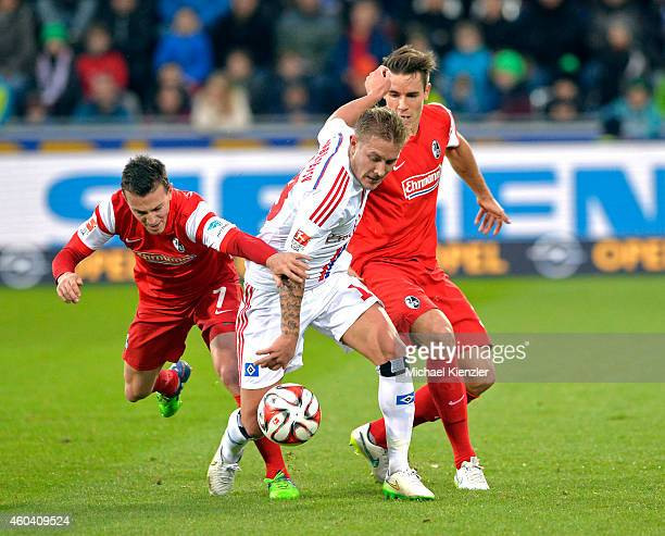 Vladimir Darida and Christian Guenter of Freiburg challenges Lewis Holtby of Hamburger SV during the Bundesliga match between SC Freiburg and...