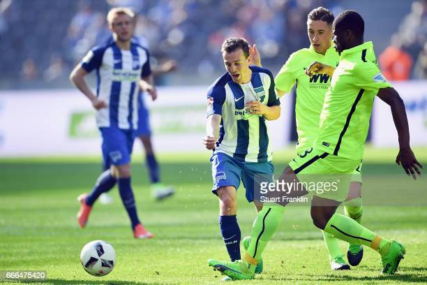 Vladimir Darida of Berlin is challenged by Dominik Kohr and Kevin Danso of Augsburg during the Bundesliga match between Hertha BSC and FC Augsburg at...