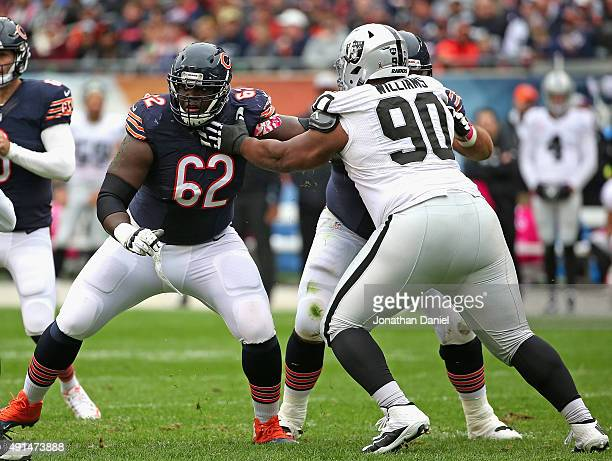 Vladimir Ducasse of the Chicago Bears looks to block Dan Williams of the Oakland Raiders at Soldier Field on October 4 2015 in Chicago Illinois The...