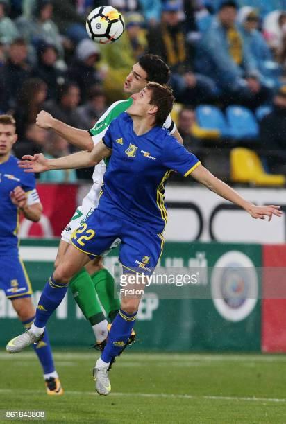 Vladimir Dyadyun of FC Rostov RostovonDon is challenged by Magomed Ozdoyev of FC Rubin Kazan during the Russian Premier League match between FC...