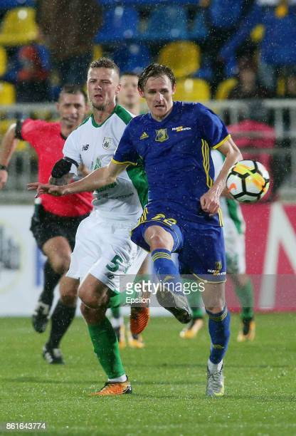 Vladimir Dyadyun of FC Rostov RostovonDon is challenged by Ragnar Sigurdsson of FC Rubin Kazan during the Russian Premier League match between FC...