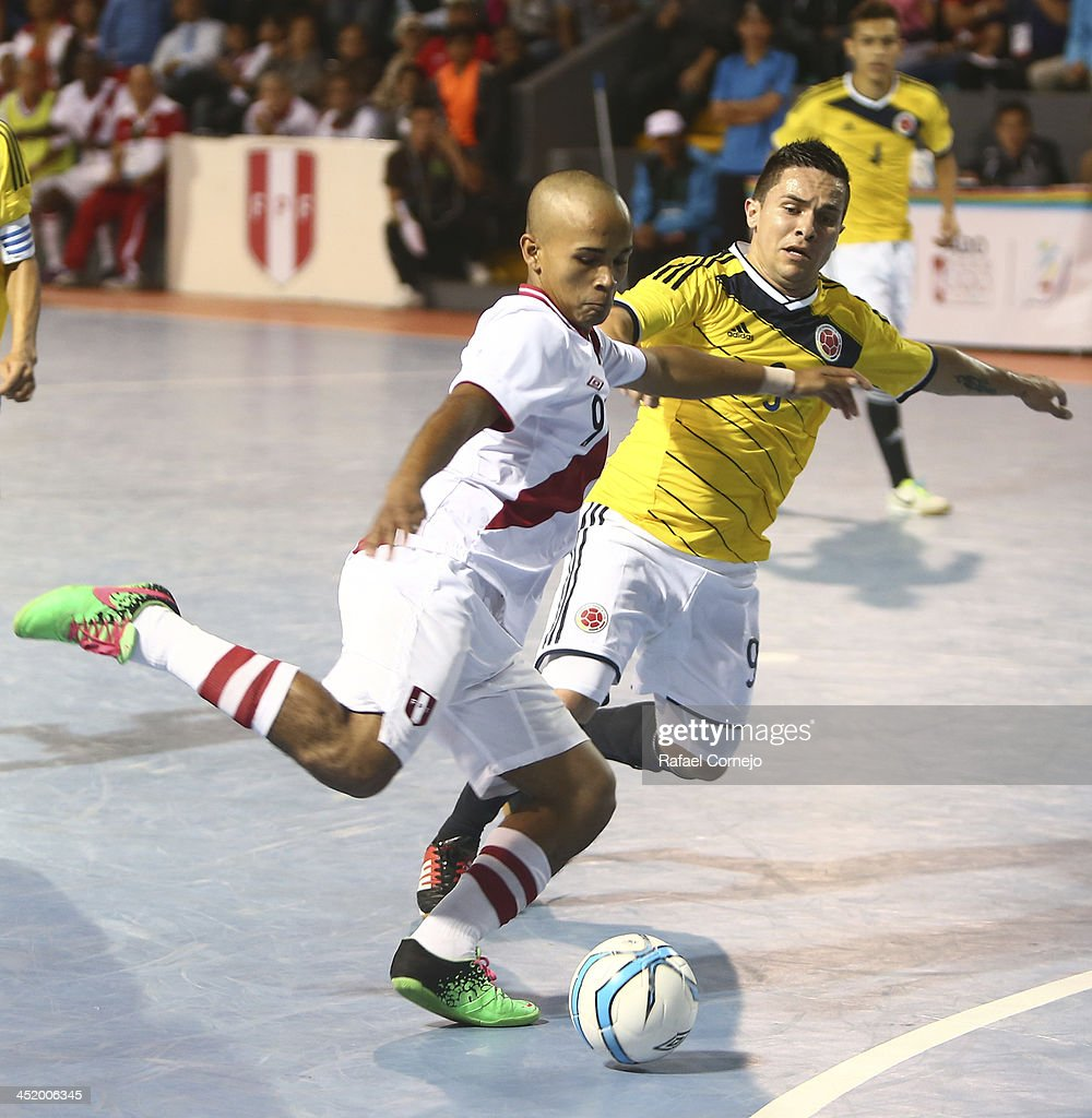 Vladimir Falla of Peru fights for the ball with Andres Reyes of Colombia during a match between Colombia and Peru as part of the XVII Bolivarian Games Trujillo 2013 at Videna San Luis on November 25, 2013 in Lima, Peru.