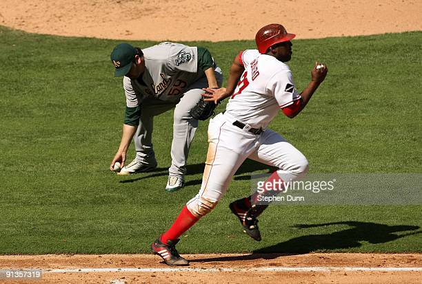 Vladimir Guerrero of the Los Angeles Angels of Anaheim runs to first as pitcher Edgar Gonzalez of the Oakland Athletics fields his ground ball on...