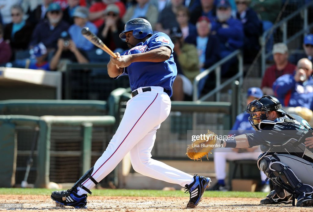 Vladimir Guerrero of the Texas Rangers bats as Adam Moore of the Seattle Mariners catches during a spring training game against the Seattle Mariners...
