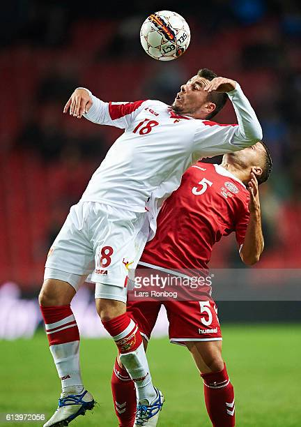 Vladimir Jovovic of Montenegro and Riza Durmisi of Denmark compete for the ball during the FIFA World Cup 2018 european qualifier match between...