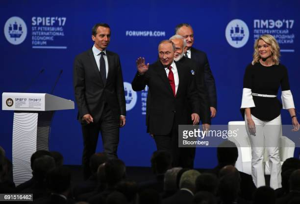 Vladimir Putin Russia's president center waves to the audience as he arrives with Narendra Modi India's prime minister center right and Christian...