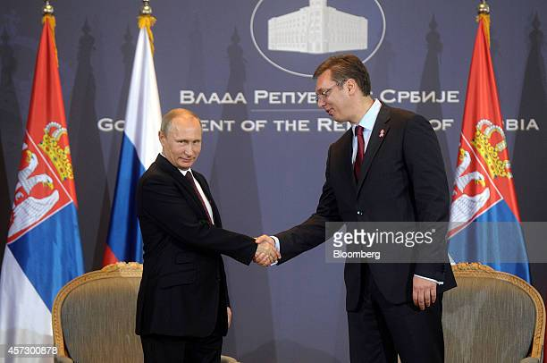 Vladimir Putin Russia's president left and Aleksandar Vucic Serbia's prime minister shake hands ahead of their meeting in Belgrade Serbia on Thursday...