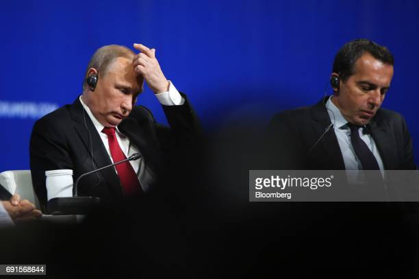 Vladimir Putin Russia's president left and Christian Kern Austria's chancellor sit on the panel at the plenary session during the St Petersburg...
